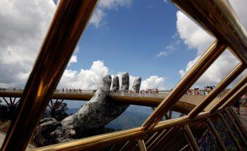 Tourists walk near giant hand structure on Gold Bridge on Ba Na hill near Danang city, Vietnam August 1, 2018. REUTERS/Kham